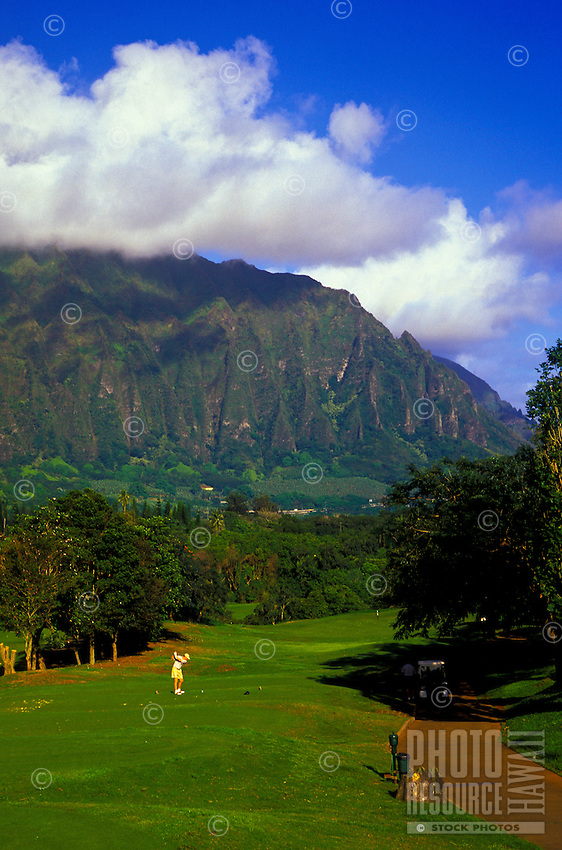 Fluted cliffs of the Koolau mountain range tower over a golfer teeing off at the picturesque Koolau Golf Course on Oahu