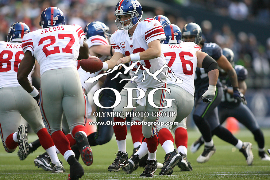 November 07, 2010:  New York Giants quarterback #10 Eli Manning sets to hand the ball off to running back #27 Brandon Jacobs against the Seattle Seahawks at Quest Field in Seattle, WA.  New York won 41-7 over Seattle.