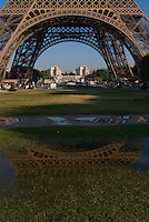 Eiffel Tower and her reflection in small puddle. Paris. Trocadero visible through the tower legs.  Shot from Champs de Mars. Early morning, clear, cloudless sky