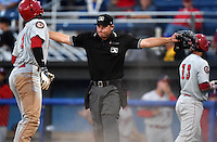 Umpire Christopher Stump signals safe on an in the park home run during a game between the Auburn Doubledays and Batavia Muckdogs on August 27, 2014 at Dwyer Stadium in Batavia, New York.  (Mike Janes/Four Seam Images)