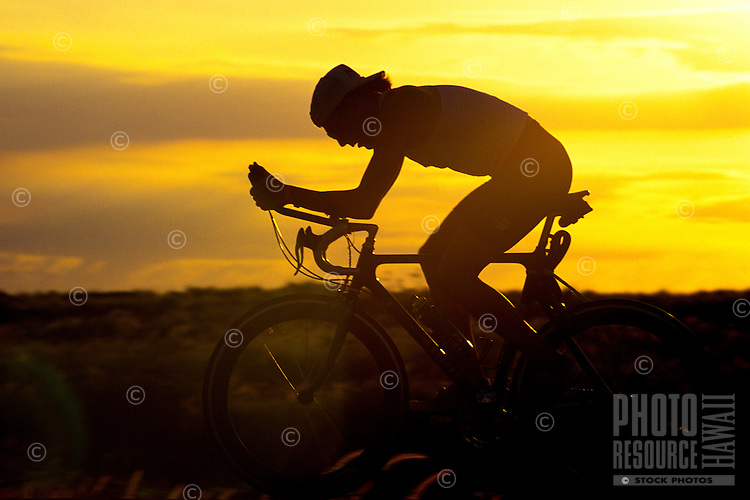 Side view of a bicyclist silhouetted against the sunset at the Ironman Triatholon on the Big Island of Hawaii.