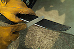 Using a flat file to sharpen a machete.