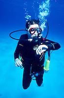 DIVERS<br /> Checks dive computer<br /> Diver wearing scuba diving equipment underwater.