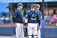 Asheville Tourists starting pitcher Alejandro Requena (15), catcher Brian Serven (25), and pitching coach Ryan Kibler (9) have a conference on the mound during a game against the Hickory Crawdads at McCormick Field on July 13, 2017 in Asheville, North Carolina. The Tourists defeated the Crawdads 9-4. (Tony Farlow/Four Seam Images)