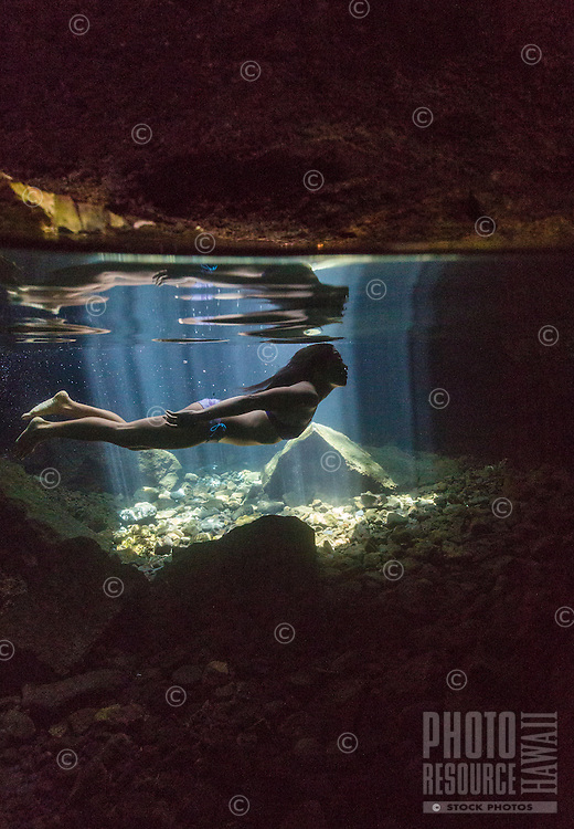A woman explores a collapsed lava tube swimming hole on the Big Island of Hawai'i.