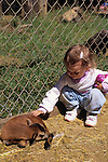 Young girl petting a baby goat at the West Coast Game Park Bandon Oregon State USA.