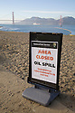 A beach closed sign stands at Crissy Field and an oil spill containment boom floats in the San Francisco Bay while a  container ship passes under the Golden Gate Bridge in the background (11/12/07). On November 7, 2007 the Cosco Busan container ship spilled an estimated 58,000 gallons of bunker fuel into San Francisco Bay after striking a tower of the San Francisco-Oakland Bay Bridge.