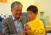 ASIAN-AMERICAN (CHINESE) GRANDFATHER AND GRANDSON PLAYING CHINESE CHESS AT HOME. GRANDFATHER AND GRANDSON. SAN FRANCISCO CALIFORNIA.