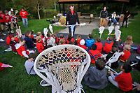 Young athletes listen to coaches before a lacrosse clinic and practice at a city park in Westerville, OH.