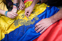 A group of young women smoke marijuana over Colombia's flag in the streets of Medellin city. In the frame of the International Day of the Marijuana and for the legalization In Medellin, Colombia, May 5, 2012. Photo by Fredy Amariles/VIEWpress.