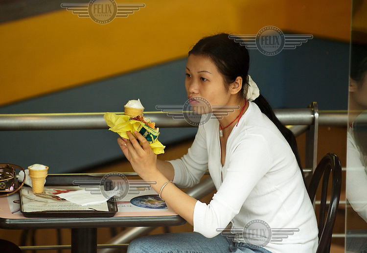 A young woman in McDonald's eating a hamburger and an ice cream at the same time, taking alternate bites.