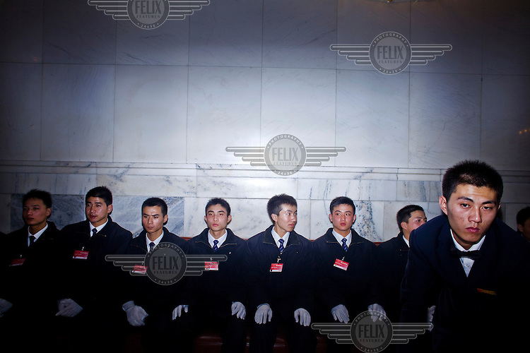 Attendants wait for directions as they sit in the Great Hall of the People after the Chinese People's Political Consultative Conference (CPPCC), plenary session for the NPC (National People's Congress).