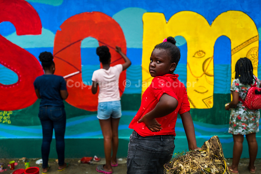 """Afro-Colombian female students paint a society and environment-related mural on a school wall in Quibdó, Colombia, 5 October 2019. Supervised by a Bogotan street artist named Guache, a group of young activists from Chocó department created a large artwork called """"Somos Atrato"""" (""""We are [the river] Atrato"""") celebrating the Afro-Colombian heritage and accenting the inherent link between the communities and the river Atrato in the Pacific region of Colombia."""