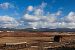 A decaying barn sits against the backdrop of the Anaconda mountain range on a bright sunny day with puffy white clouds.