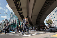 Japanese salarymen under a large expressway flyover near Kanda in Tokyo, Japan. Friday February 20th 2015