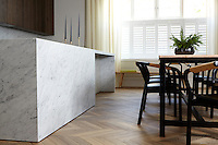 In the spacious kitchen/dining room the chevron flooring is made of French reclaimed oak whilst the unfussy furniture has a retro feel. An impressive marble kitchen island provides plenty of workspace.