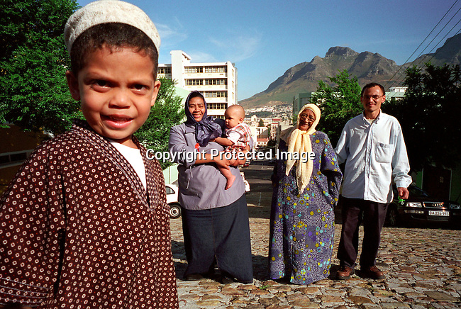 dipolit00037.Land reform. Fejrus with baby and Miriam (old woman) and Husband of Fejrus and their son (foreground) on November 29, 2002 outside their current home in Bo-Kaap, a muslim area in central Cape Town, South Africa. Miriam is one of the first people that will return to Distrixt 6, an area in central Cape Town where they were forced out of during the old apartheid regime. New houses are soon being built. Family..©Per-Anders Pettersson/ iAfrika Photos.....