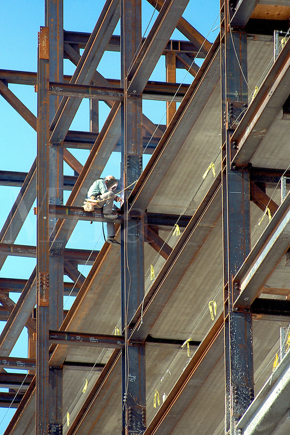 welder or steelworker working high up on the steel girders of the construction site of a high rise hotel. United States.