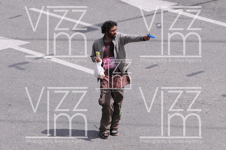 MEDELLÍN-COLOMBIA-16-08-2012. Un indigente llama la atención con un arma de juguete en una calle de la ciudad./ A homeless is drawing attention with a toy gun in a street of the city.   Photo: VizzorImage/Luis Benavides.