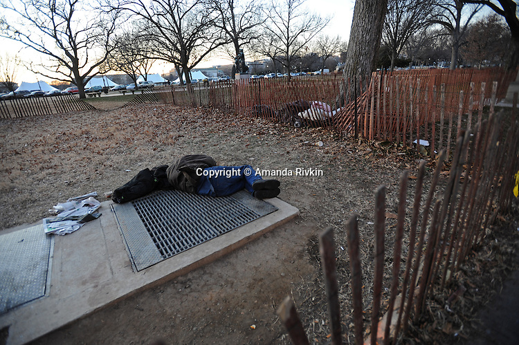 A homeless man sleeps on a warm grate to stay warm near the front of the White House as hundreds of thousands are expected in the capitol ahead of Barack Obama's inauguration as the 44th U.S. President in Washington DC on January 16, 2009.