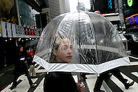 NEW YORK - MARCH 31: A pedestrian walks across 7th Avenue carrying an umbrella in Times Square March 31, 2004 in New York City. The Great White Way requires clean sight lines, and this clear umbrella is the perfect rainy-day accessory.  Times Square's 100th birthday is April 8, 2004. On April 8, 1904, Mayor George McClellan signed a resolution changing the name of Long Acre Square to Times Square. Times Square, a living icon of popular culture, is one of the most familiar and most frequently reproduced fragments of urban real estate on the planet. (Photo by Landon Nordeman, 2004).