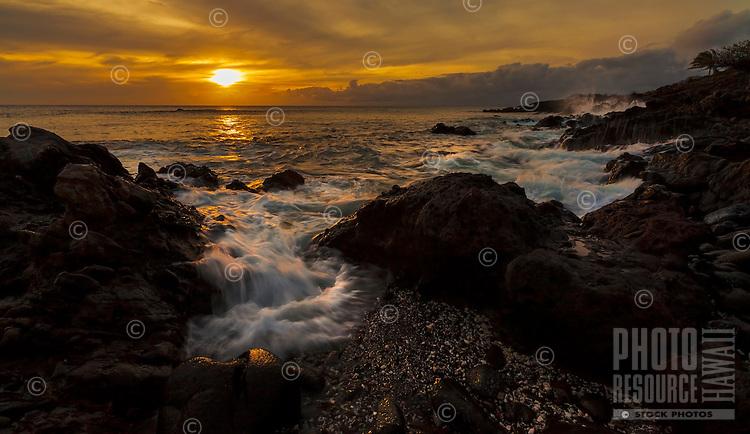 At sunset, waves rush along the rugged coastline near Mahukona on the Big Island of Hawai'i.