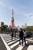 Pedestrians cross a busy road near to Tokyo Tower.