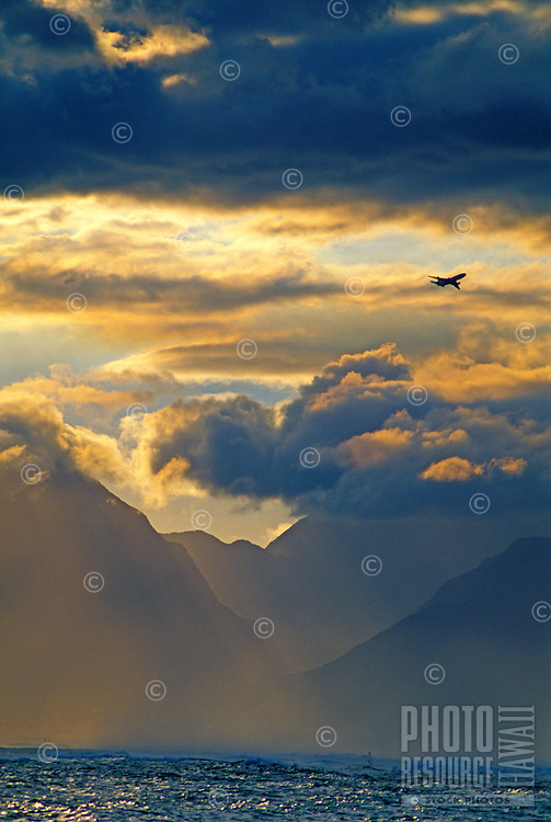 An airplane take off at sunset from the Kahului Airport on Maui's North Shore, with dramatic clouds above the West Maui Mountains, Iao Valley and rough ocean.