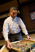 "Tokubee Masuda, CEO of the Tsukinokatsura sake brewery. He is looking at a woodblock print showing sake brewing in Fushimi during the Edo Period. Fushimi, Kyoto, Japan, October 10, 2015. Tsukinokatsura Sake Brewery was founded in 1675 and has been run by 14 generations of the Masuda family. Based in the famous sake brewing region of Fushimi, Kyoto, it has a claim to be the first sake brewery ever to produce ""nigori"" cloudy sake. It also brews and sells the oldest ""koshu"" matured sake in Japan."