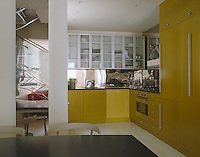 The use of a mirrored splashback creates the illusion of depth in this compact yellow kitchen