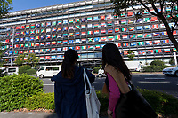 Two women look at the Offices of the Mainichi Newspaper Company display all 206 flags of the countries taking part in the 2020 Tokyo Olympic Games. Chiyoda, Tokyo, Japan. Friday October 27th 2017. Saturday October 28th marks 1,000 days before the opening ceremony of the Summer Olympics in Tokyo. Each flag is 210 centimeters wide and 140 centimeters high and is being draped over windows on the south side of the building, facing the Imperial Palace