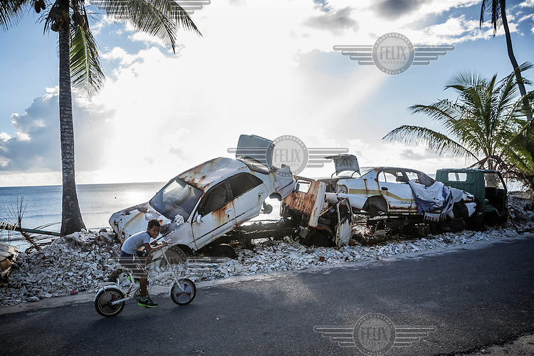A boy rides his bicycle past a pile of wrecked vehicles.