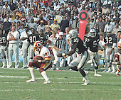 Washington Redskins wide receiver Charlie Brown (87) makes a reception against the Los Angeles Raiders at RFK Stadium in Washington, D.C. on October 2, 1983.  Covering on the play for the Raiders is James Davis (45) as his teammate right outside linebacker Rod Martin (53) looks on.  The Redskins won the game 37 - 35.<br /> Credit: Howard L. Sachs / CNP