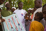 An HIV/AIDS prevention volunteer talks to men in Yankaba market in Kano, Nigeria, about how partner reduction reduces chances of HIV/AIDS transmission.  He uses a pictoral flipchart designed for low-literacy audiences by the Society for Family Health (SFH), Nigeria's largest indigenous non-profit and affiliate of the international social marketing organization, Population Services International (PSI).