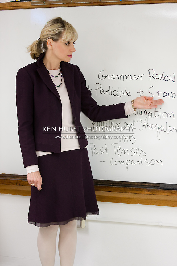 Woman teacher or instructor in a college, university, high school, middle school, elementary classroom pointing to writing on white board.