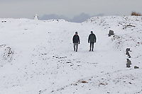 WEATHER PICTURE WALES<br /> Pictured: A couple walk near a snowman on the snow covered Black Mountains near Brynamman, Wales, UK. Wednesday 23 January 2019