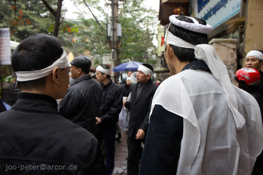 funeral procession with people wearing white headbands as symbol of death and mourning,streets of Hanoi, Vietnam