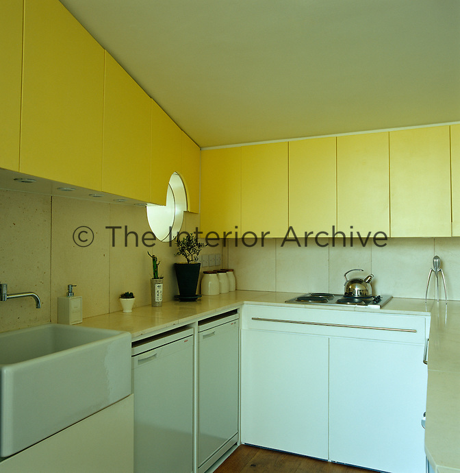 The compact kitchen features sleek flat-fronted units, a porthole window and a limestone work surface and splashback