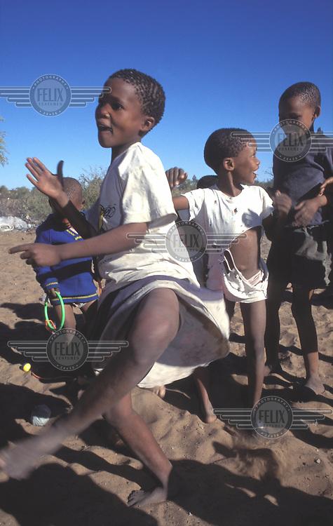 © Paul Weinberg / Panos Pictures..Bushmanland, Ghansi, BOTSWANA...San Bushman kids dancing.