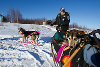 Long-time volunteer Jim Paulus backs up DeeDee Jonrowe's sled to help her park at the Iditarod checkpoint during the 2011 Iditarod race.  Dee's dog *Smoke* is riding in the basket.