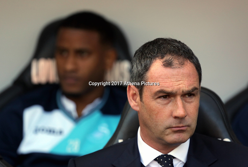 SWANSEA, WALES - APRIL 22: (L-R) Luciano Narsingh Swansea City and manager of Swansea City, Paul Clement sit in the dug out during the Premier League match between Swansea City and Stoke City at The Liberty Stadium on April 22, 2017 in Swansea, Wales. (Photo by Athena Pictures/Getty Images)