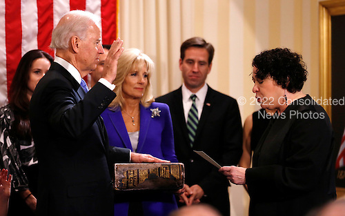 United States Vice President Joe Biden (L) takes the oath of office from Supreme Court Justice Sonia Sotomayor as his wife Jill Biden holds the family bible while family members look on at the U.S. Naval Observatory in Washington January 20, 2013.   .Credit: Kevin Lamarque / Pool via CNP