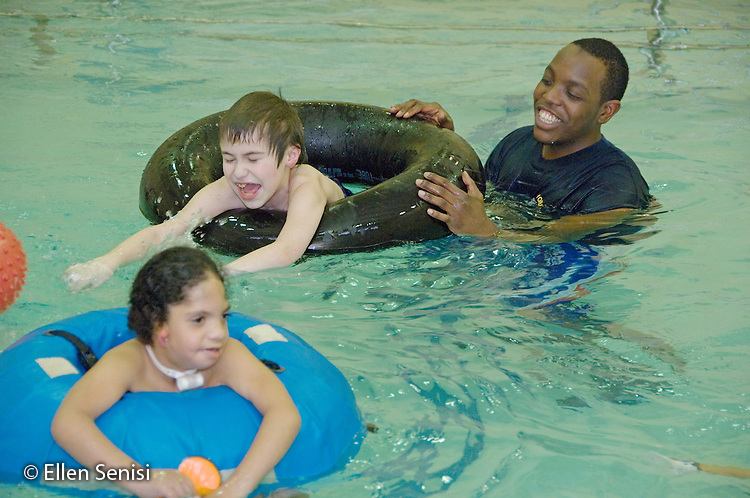 MR / Albany, NY.Langan School at Center for Disability Services .Ungraded private school which serves individuals with multiple disabilities.Two boys in tubes play in the pool while teaching assistant (African-American) supervises. Boy in Water Walker: 7, African-American, Pierre Robin syndrome, limited verbal output with expressive and receptive language delays; Boy in black tube: 10, Duchenne muscular dystrophy, expressive and receptive language delays.MR: Smi24, Bud2, Wes2.© Ellen B. Senisi