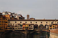 Firenze: A classic view of Ponte Vecchio (the Old Bridge), over the Arno river, with its old peculiar buildings, in the historical center of the town. The photo gives back the colorful atmosphere typical of the place, that is among the town landmarks. There are quite a lot of tourists, too.