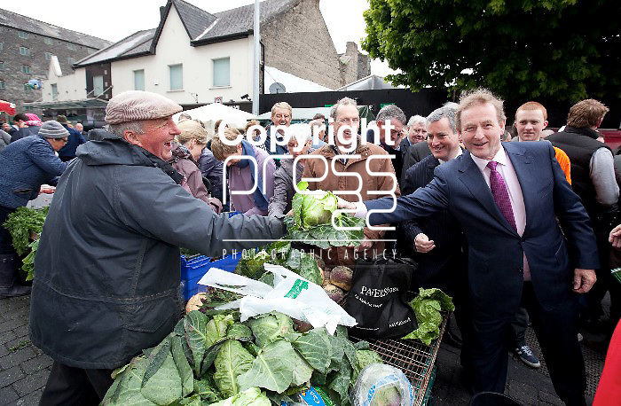 Taoiseach Enda Kenny T.D get a head of Cabbage from a Vender  in the Milk Market in  Limerick while canvassing for the yes Vote Pictured Credit Brian Gavin Press 22