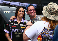 Mar 29, 2014; Las Vegas, NV, USA; NHRA funny car driver Alexis DeJoria poses with a fan for a picture during qualifying for the Summitracing.com Nationals at The Strip at Las Vegas Motor Speedway. Mandatory Credit: Mark J. Rebilas-