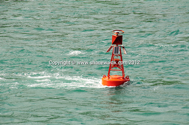 The tide flows at up to 4 to 5 knots in the Tauranga harbour entrance, flowing past the channel marker buoys.