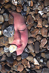 Young girl face half buried in shingle pebbles on beach, UK