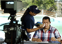 "An assistant wipes Venezuelan President Hugo Chavez's face during his weekly television broadcast ""Alo Presidente"", in La Guaira, Vargas state near Caracas, August 1, 2004. His recent 200th program could be his last if he loses a referendum on Sunday that asks Venezuelans whether they want him to quit the presidency. REUTERS/Howard Yanes ..TO GO WITH FEATURE  (IMAGE TAKEN AUGUST 01, 2004)"