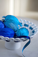 Easter eggs wrapped in striking blue foil paper in a white ceramic dish